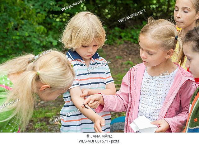Germany, Children watching caterpillar of peackock butterfly on arm of a boy