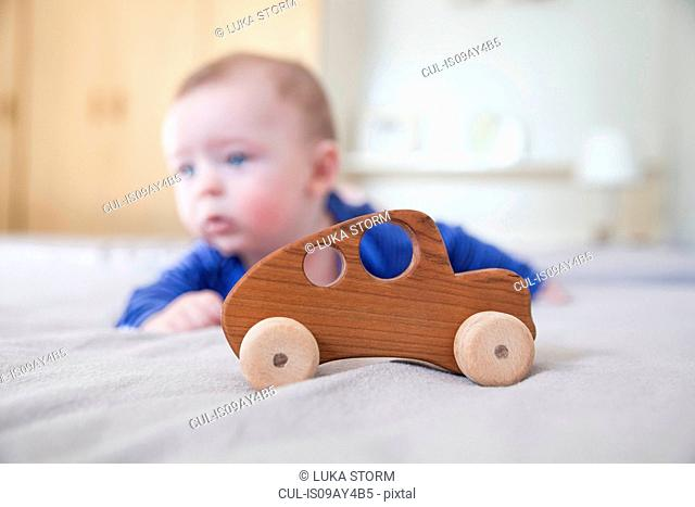 Baby boy playing on bed with wooden toy car