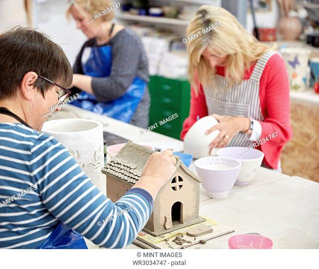 A group of people seated at a workbench in a pottery studio, decorating and shaping clay objects