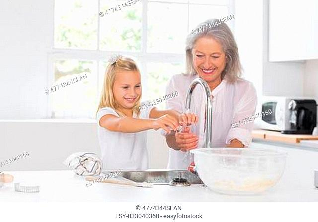 Grandmother and granddaughter washing hands in the kitchen
