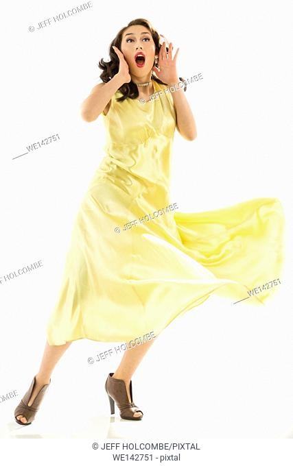 Beautiful young woman in vintage yellow dress, shouting or singing, full length in brown heels