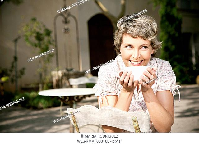 Spain, Mallorca, portrait of smiling mature woman sitting in the garden with cup of Cappuccino