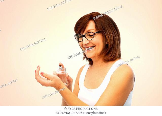 smiling senior woman spraying perfume to her wrist