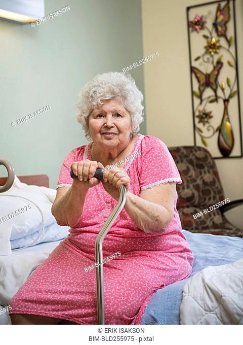 Smiling Caucasian woman sitting on bed leaning on cane