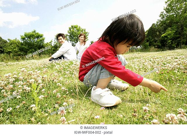 A small boy stares at the grass in the garden as his parents looks on