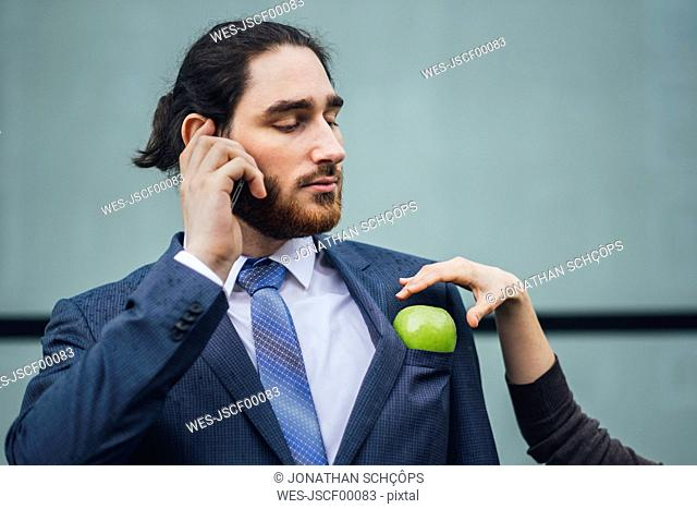 Businessman talking on cell phone and woman placing an apple in his jacket pocket