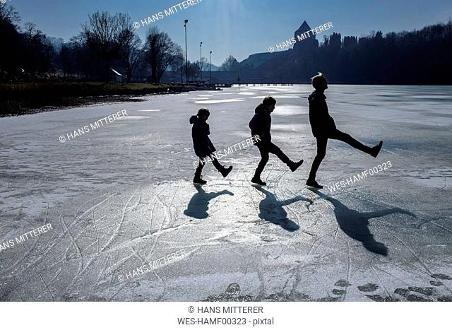 Three children playing on icy surface
