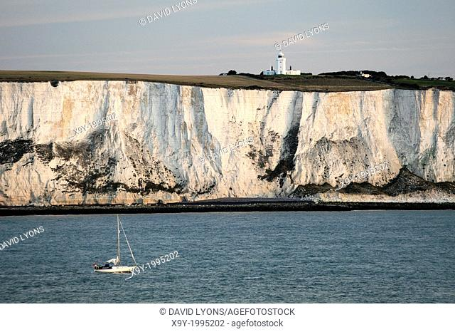 Yacht passing along the White cliffs of Dover in the English Channel east of Dover below South Foreland lighthouse. Dawn light