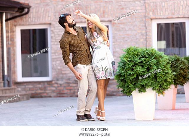 Happy young couple fooling around outdoors