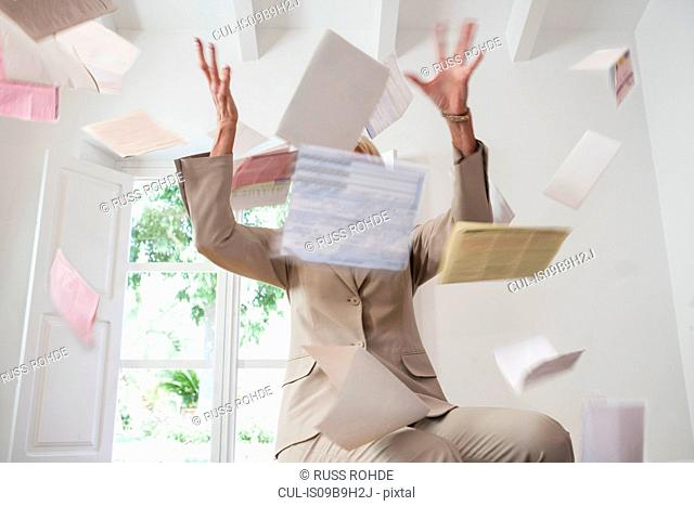 Businesswoman throwing paperwork in air