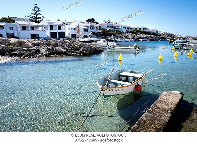 Cala Biniancolla in the early morning, boat in calm sea. Minorca, Balearic Islands, Spain