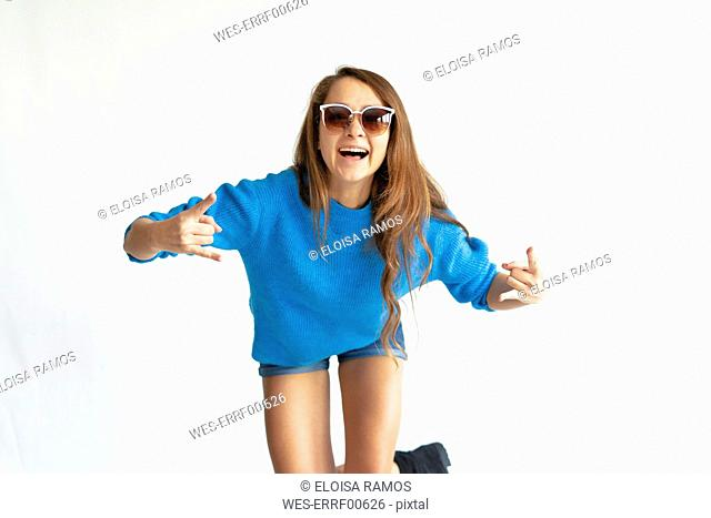 Portrait of a young woman in a blue sweater, laughing, wearing sunglasses