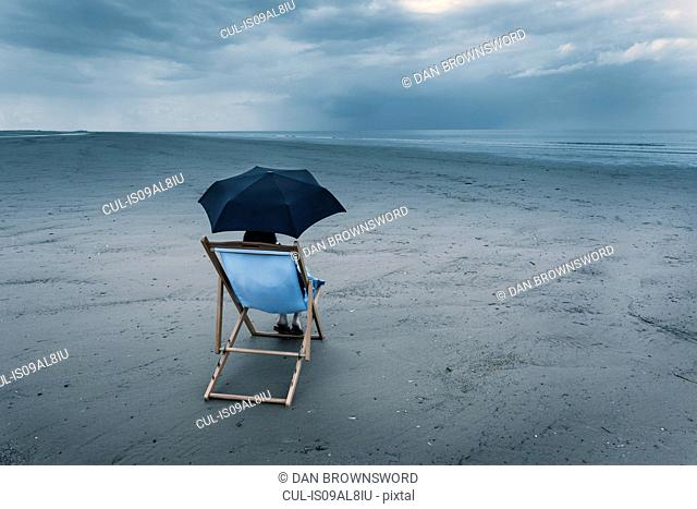 mature woman sitting on deck chair on stormy beach, under umbrella