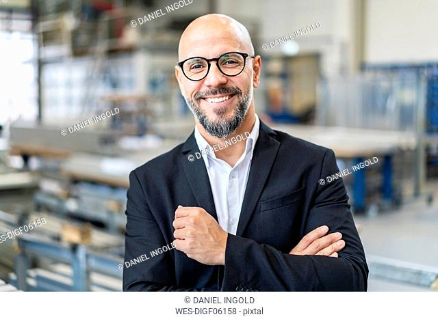 Portrait of smiling businessman in factory