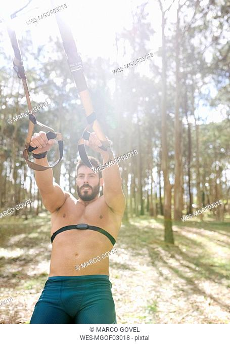 Barechested man doing suspension traning outdoors