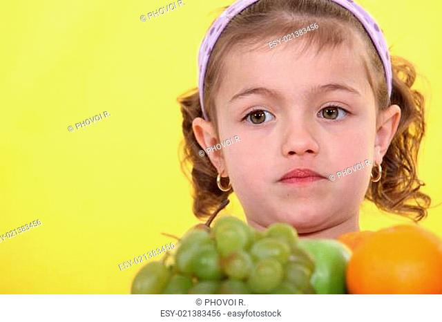 Girl with a pile of fruit