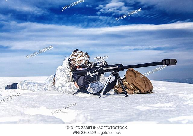 Army soldier with Sniper rifle in action in the Arctic. He lies in the snow desert, suffering from extreme cold, but waiting as long as enemies appear to kill...