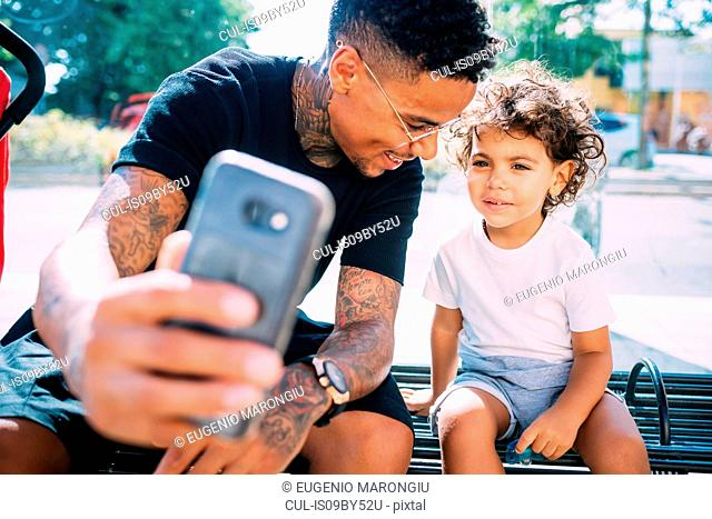 Father and son taking selfie on bench
