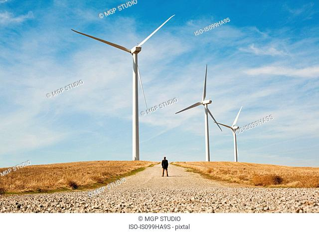 Distant view of man in front of wind turbines