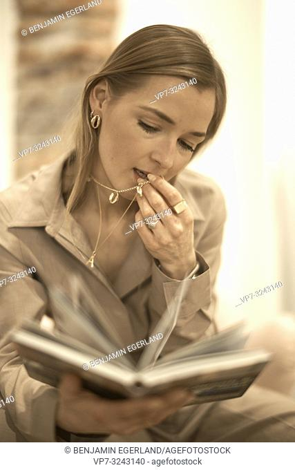 fashionable blogger woman reading book indoors, playing with expensive necklace jewellery chain, rich, wealthy woman, knowledge, in Munich, Germany