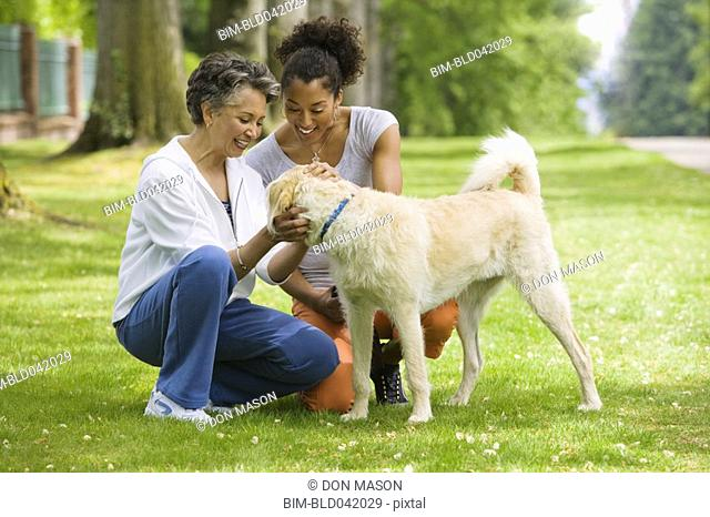 African American mother and adult daughter petting dog