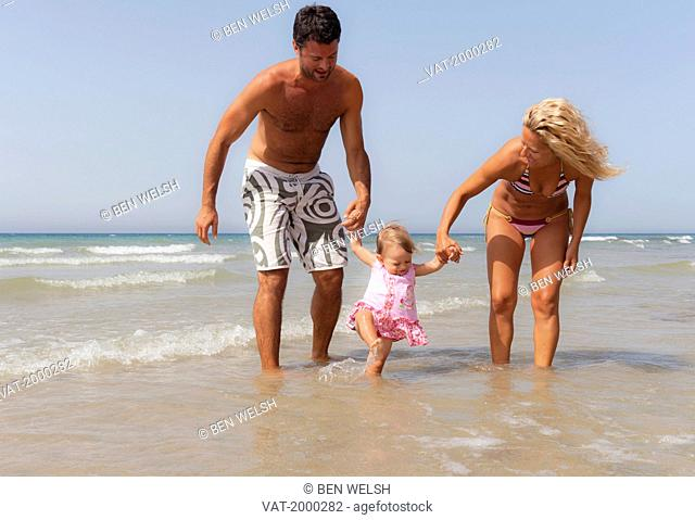 a mother and father playing with their young daughter on the beach, tarifa cadiz andalusia spain