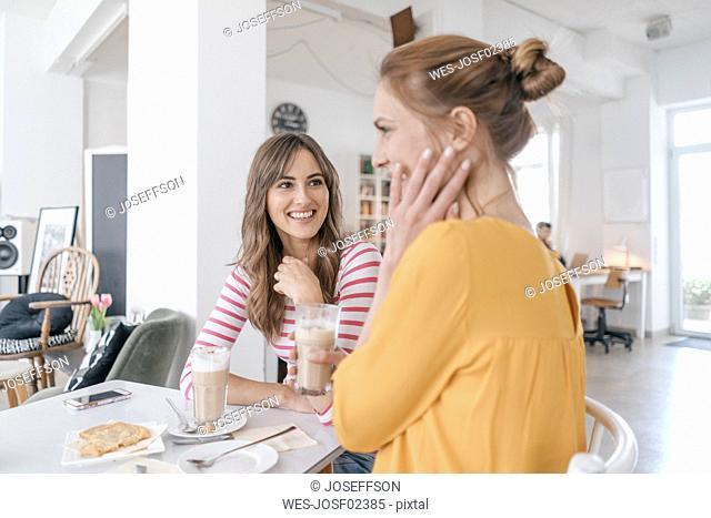 Two girlfriends meeting in a coffee shop, talking