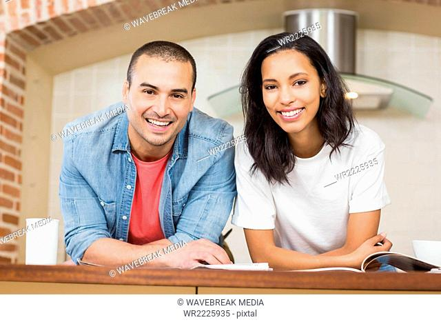 Smiling couple reading newspaper while eating cereals