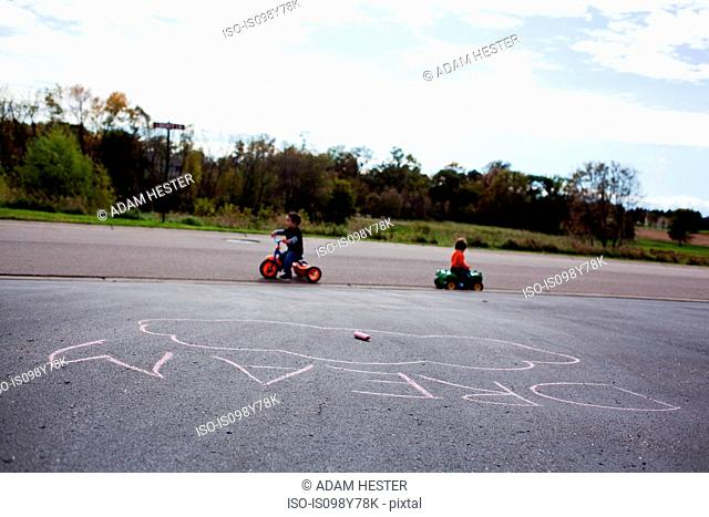 Two boys riding tricycles