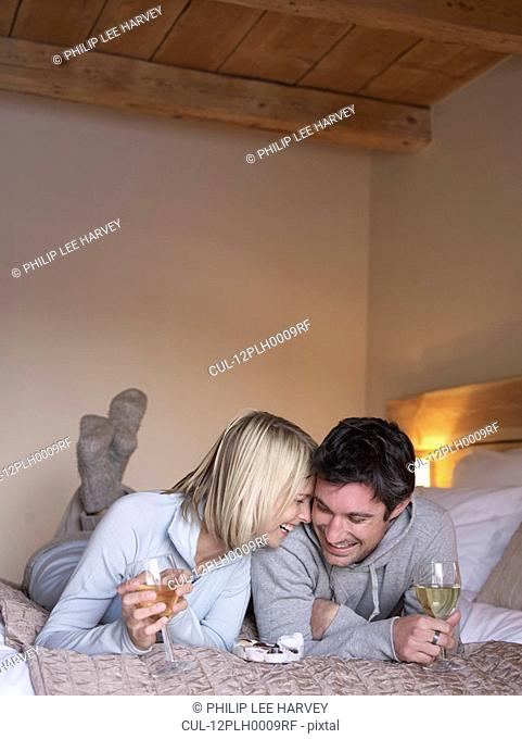 woman and man lying on bed smiling