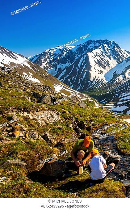 Father and son fill their water bottle near the summit of Crow Creek Pass, Chugach State Park, Southcentral Alaska
