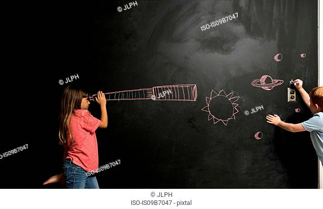 Girl looking through imaginary telescope drawn on blackboard