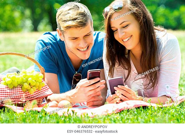 Happy Couple Using Mobile Phone While Lying In Park