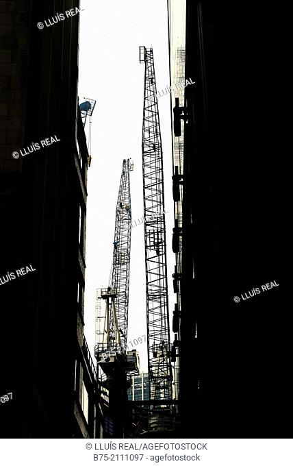 Two cranes on a construction building overlooking between two office buildings in the City of London, England, UK, Europe