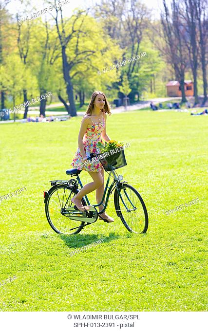 Young woman on bicycle with flowers in basket