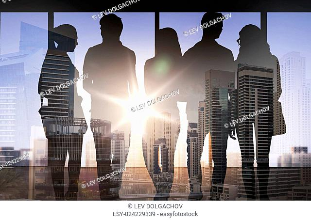 business, education, travel, tourism and people concept - people silhouettes over double exposure office and city background
