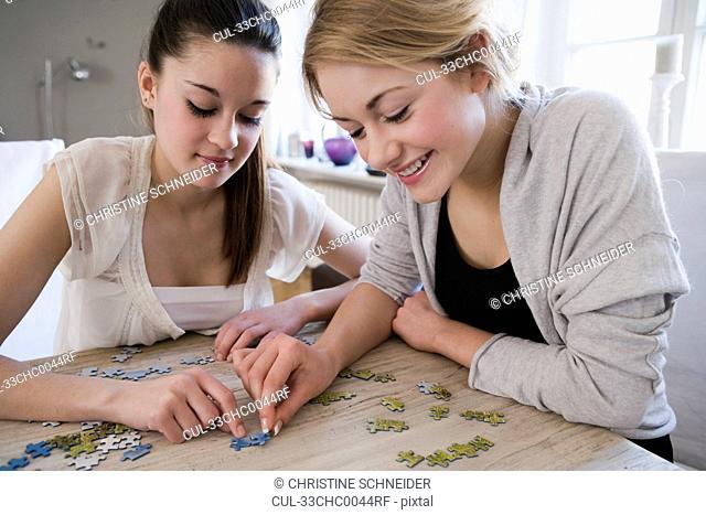 Teenage girls working on jigsaw puzzle