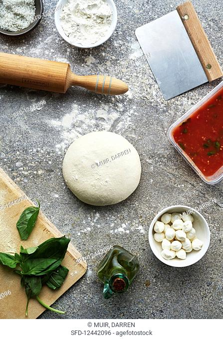 An arrangement of pizza dough and toppings (seen from above)