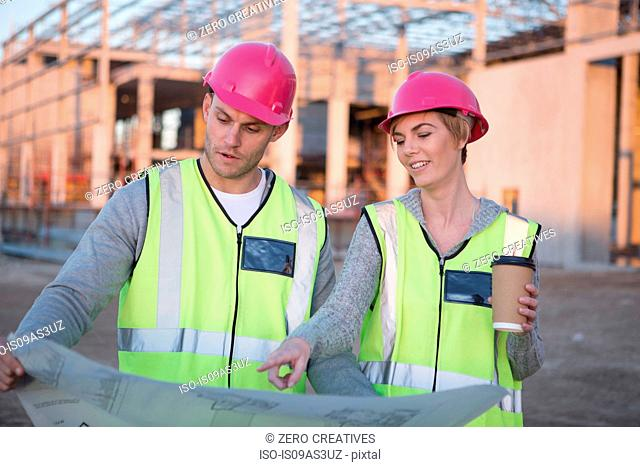Surveyor and architect pointing at blueprint on construction site