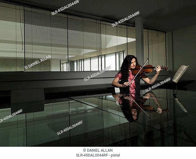 Woman playing violin in business office