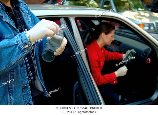 DEU, Germany, NRW: Forensic police officer looks for objects which might have been in contact with a suspect, for a later DNA analysis