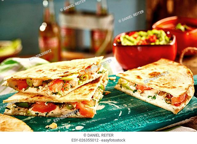 Close up of three of cooked cheese quesadillas on green cutting board with salsa and bottles in background