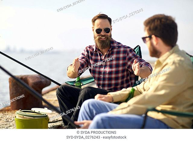 happy male friends with rods talking about fishing