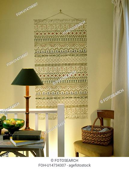 Cross-stitch wall-hanging on landing with lighted lamp on small table