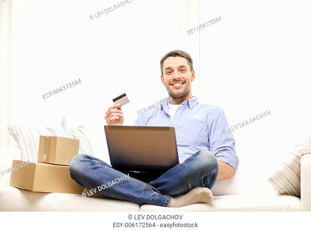 technology, home and lifestyle concept - smiling man with laptop, credit card and cardboard boxes at home
