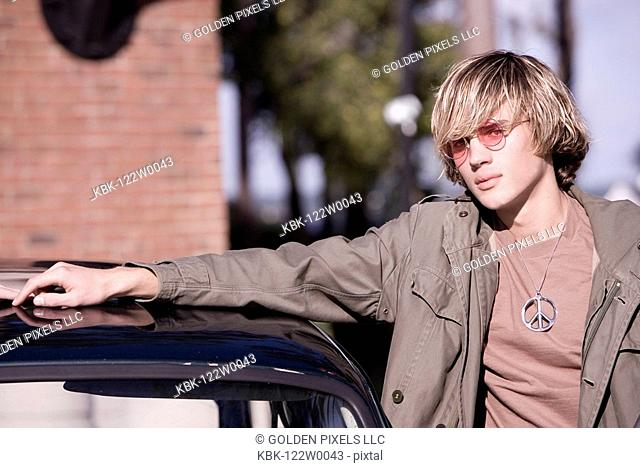 Portrait of young man in vintage 1960's hippie costume standing by a car