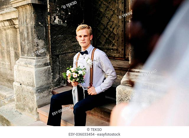 groom sitting on the stone steps and poses for the camera