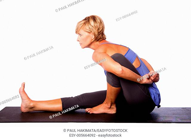 Beautiful woman in Seated Spinal Twist Marichyasana yoga pose stretching leg and spine exercise, isolated
