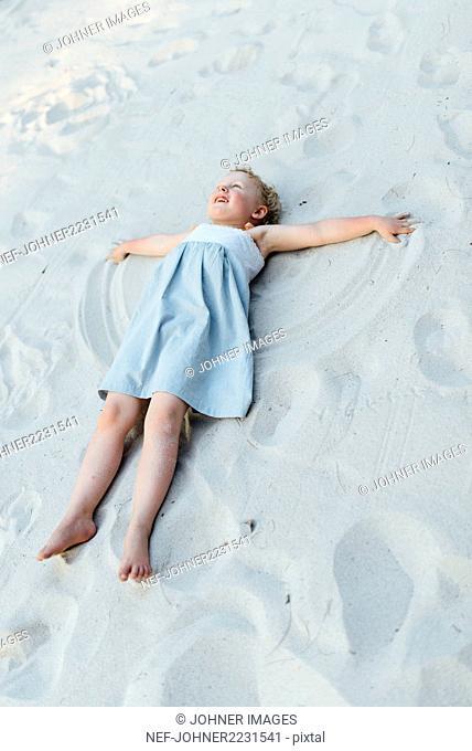 Girl making sand angel
