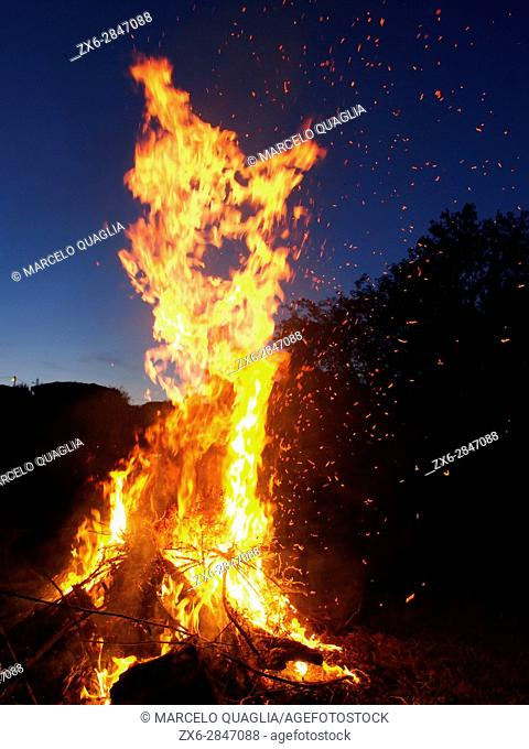 Fire sparkles while burning blackberry stems. Pisón de Fondón organic farmhouse. Villandás village. Grado council. Asturias autonomous community
